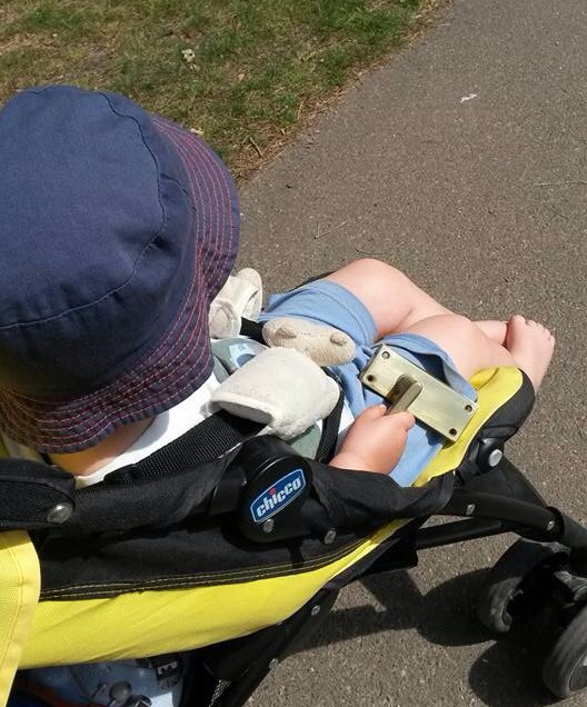 Toddler in pushchair with door handle