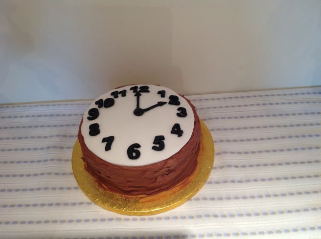 Round chocolate cake with white icing on top and black clock numbers. Clock hands pointing to two