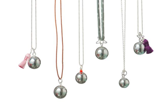 Six necklaces hanging against a white background with different colour chains and different charms. All with a silver ball pendant