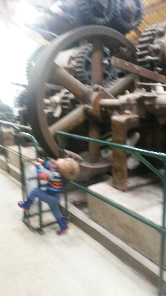 Blurry picture of son pretending some railings in a factory is a fireman's pole.