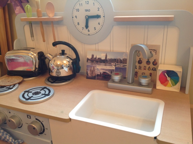 Play kitchen with clock built in, a rainbow paper clock, a clock postcard and a postcard of Westminster area