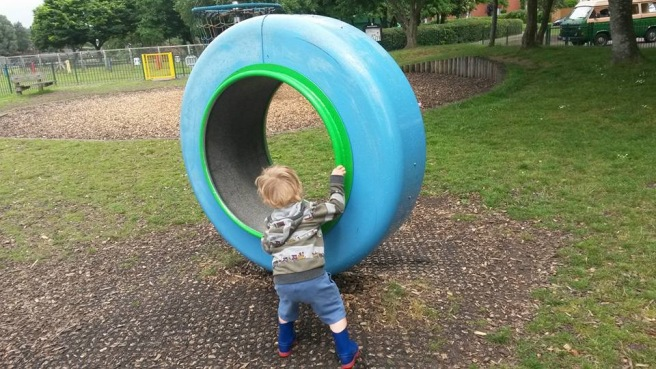 Boy spinning the spinny thing. Big ring on its side that spins