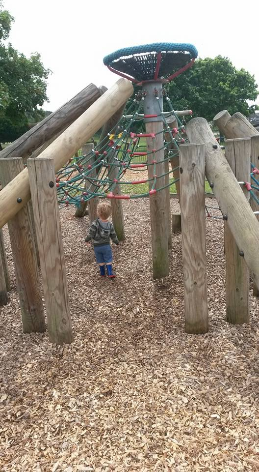 Small boy standing underneath huge rope and wooden climbing frame
