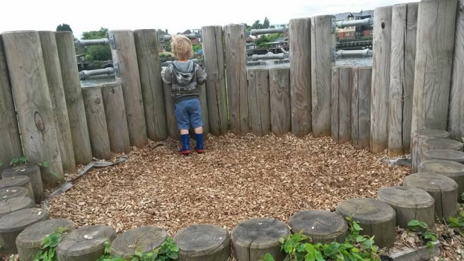Small boy peering out over the railings that look out over the river