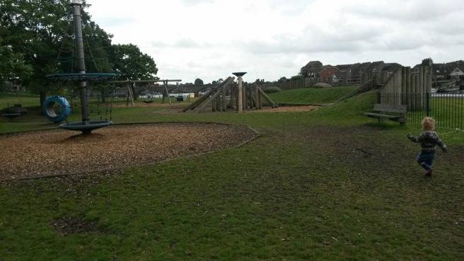 Wide shot of playground, small boy running towards equipment!