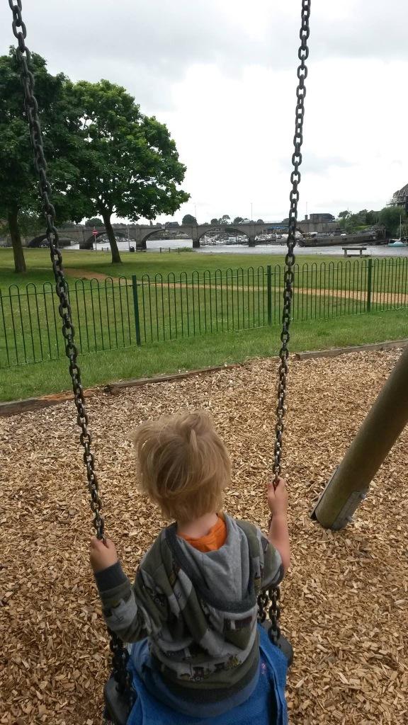 Boy on swings looking over river and road bridge