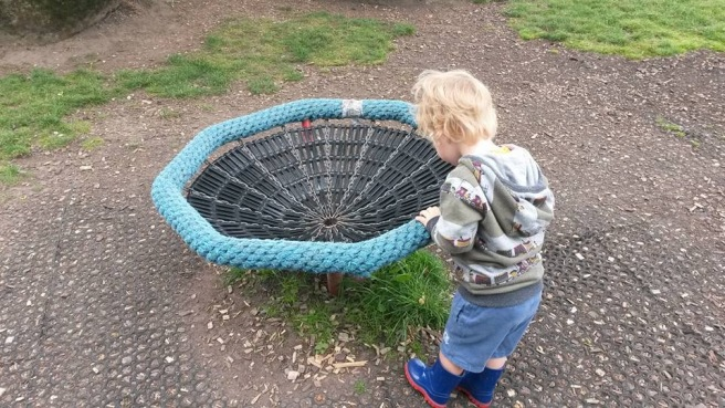 Small boy looking into spinning net thing