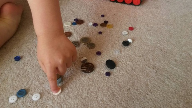 Buttons and coins and a pointing toddler finger