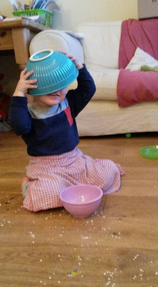 Son with bowl on his head