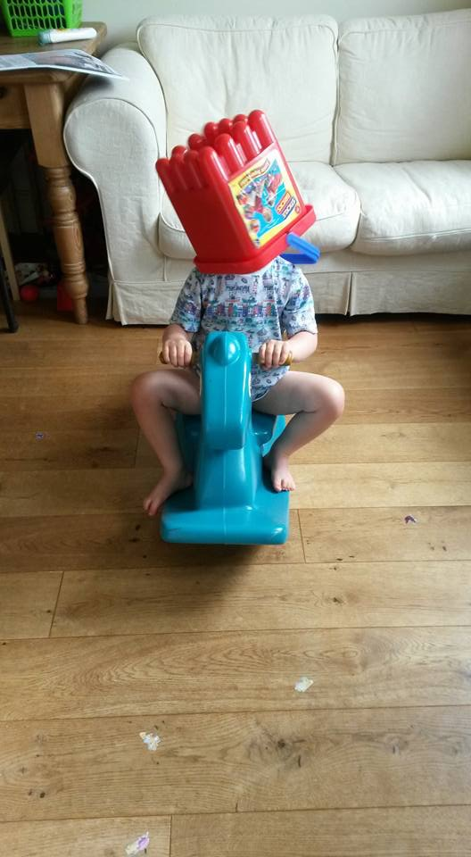 Boy on rocking horse with box on head