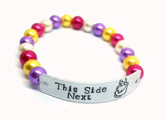 Beaded bracelet with metal band. Text on band says 'this side next'