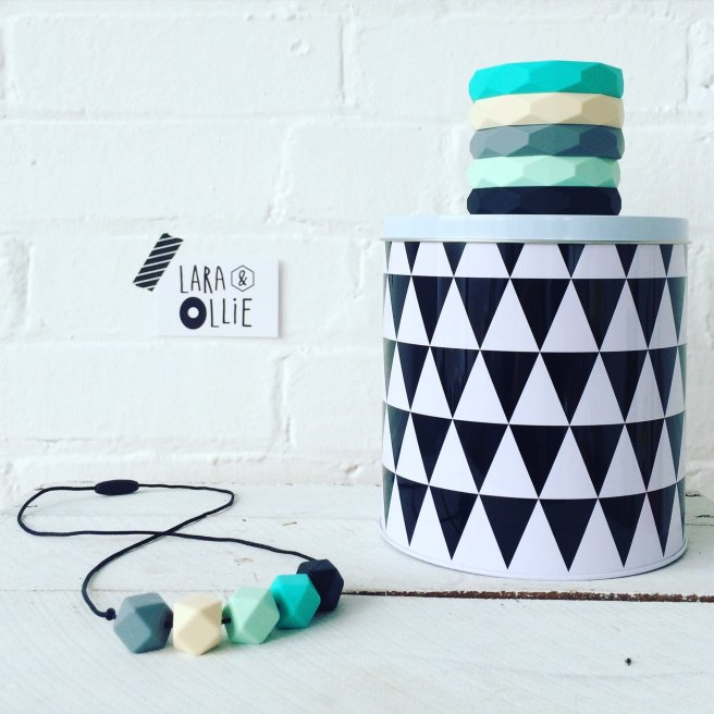 Stack of bangles on a black and white box next to a teething necklace in same colours of green and blues.