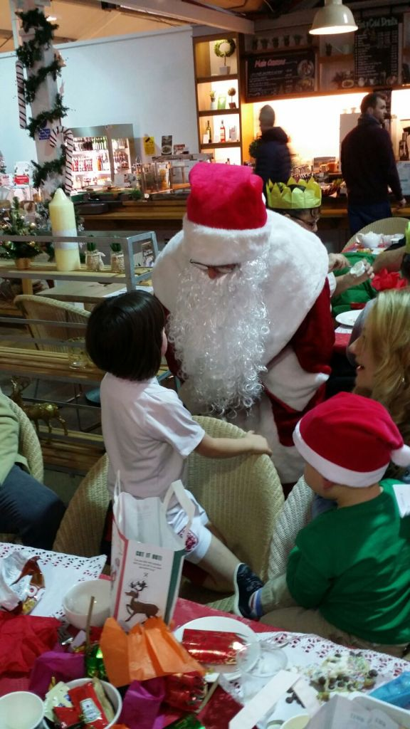 Father Christmas chatting to a girl kneeling on a chair
