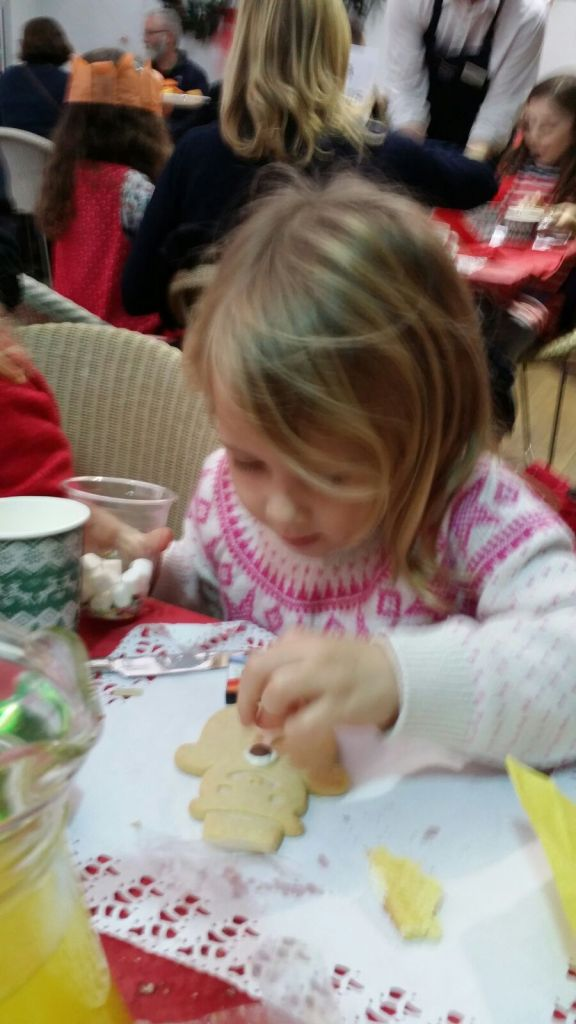 Little girl decorating snowman cookie