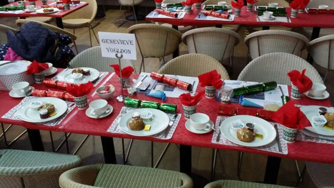 Table set with scone, teas, red tablecloth, crackers