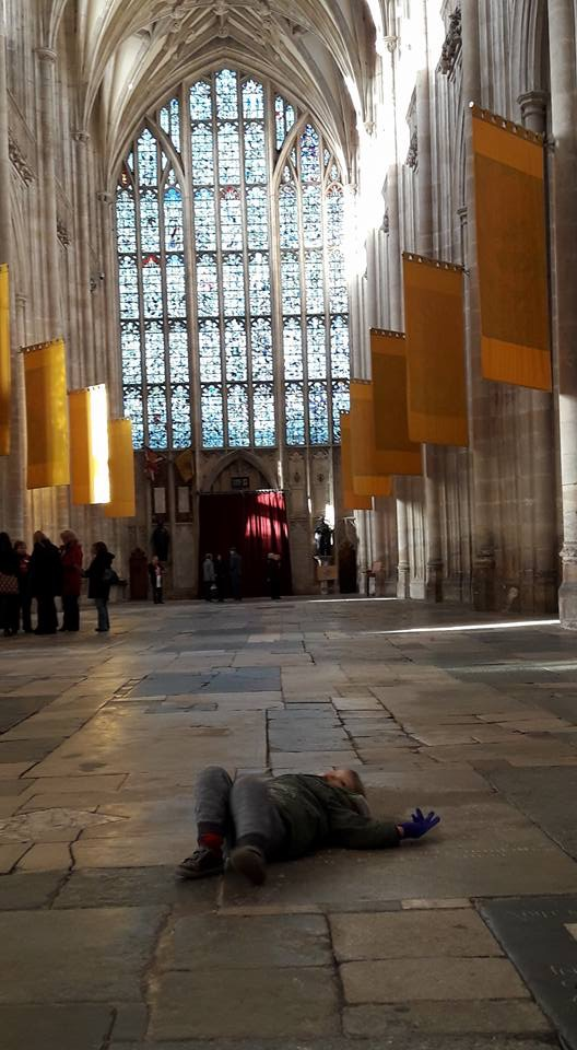 Small boy sprawled out on the floor in a cathedral