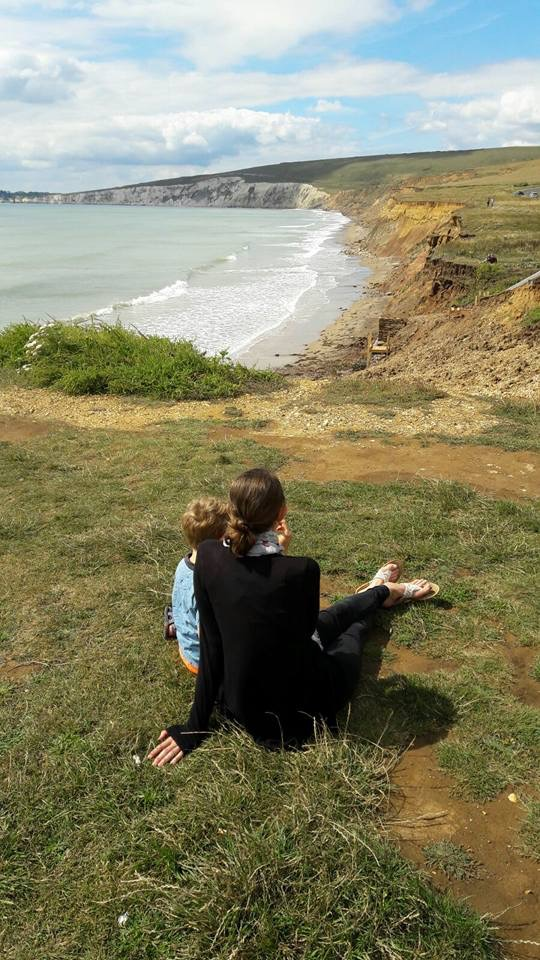 Mother and son sat on hill looking out to shoreline/cliffs and sea. Orangey soil and hills. Mother in black and boy in blue.